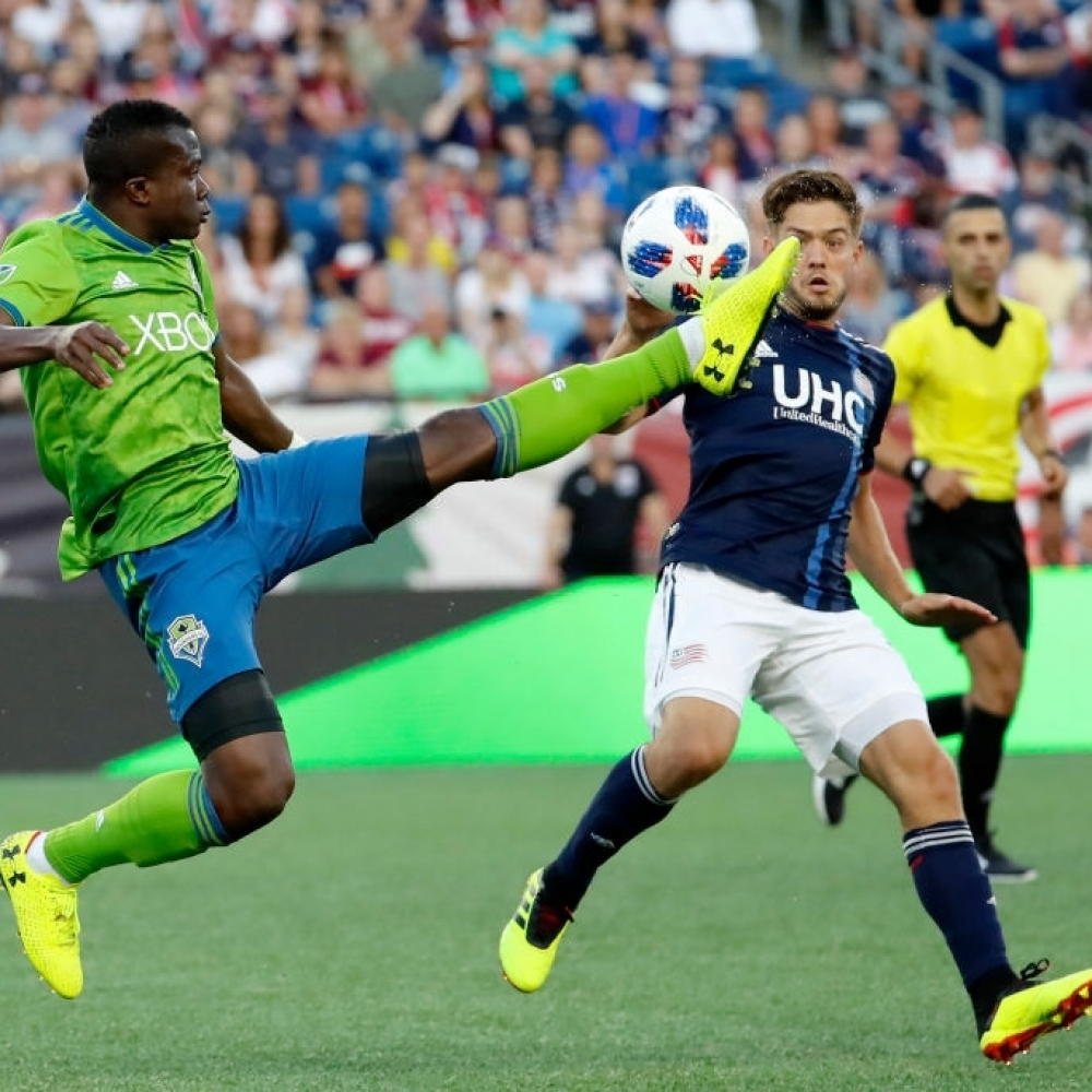 FOXBOROUGH, MA - JULY 07: Seattle Sounders FC defender Nouhou Tolo (5) plays the ball in front of New England Revolution midfielder Kelyn Rowe (11) during a match between the New England Revolution and Seattle Sounders FC on July 7, 2018, at Gillette Stadium in Foxborough, Massachusetts. The teams played to a scoreless draw. (Photo by Fred Kfoury III/Icon Sportswire via Getty Images)